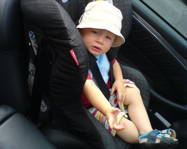 Dítě sedící v autosedačce připoutané bezpečnostním pásem